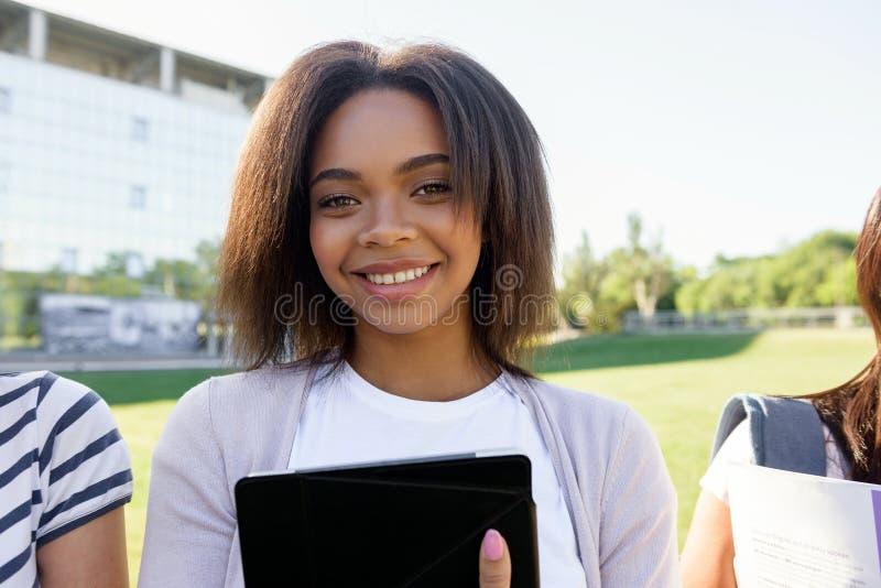 站立微笑的学生非洲的妇女户外 免版税图库摄影