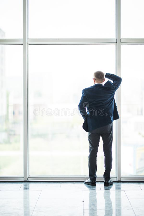 站立微笑的资深的商人画象看在办公室窗口外面用他的在他的后的手 免版税图库摄影
