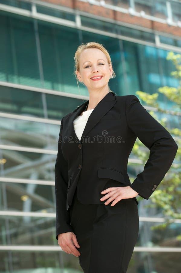 站立愉快的女商人户外 免版税库存图片