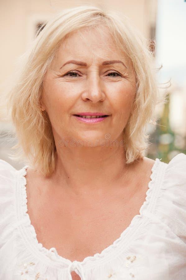 站立愉快的资深的妇女室外 美满的妇女微笑和l 免版税库存照片