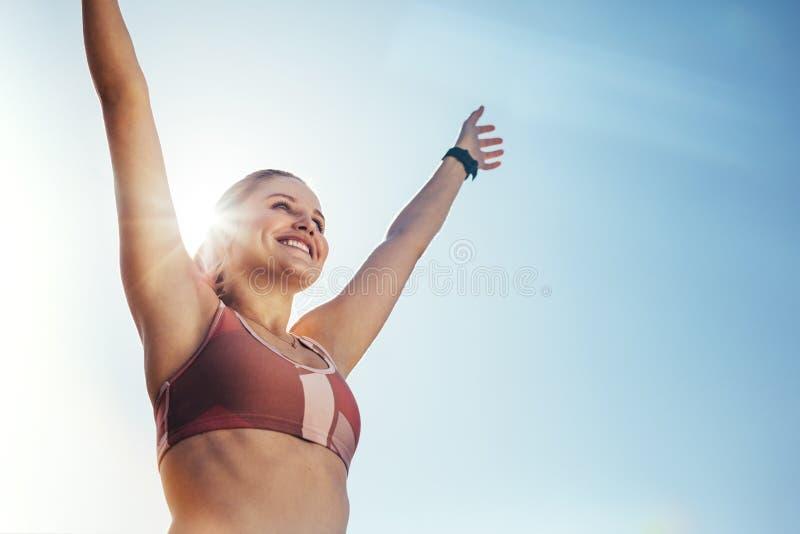 站立户外与太阳的低角度观点的一个女运动员在背景中 做锻炼的健身妇女户外与清楚 免版税库存图片