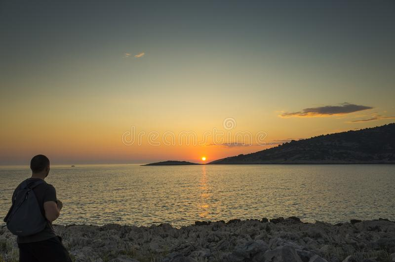 站立户外关闭的男性人美丽的自然和风景照片海洋在日落 库存照片