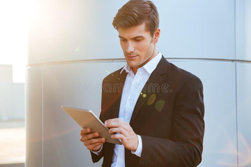 站立户外和使用个人计算机片剂的可爱的年轻商人 图库摄影