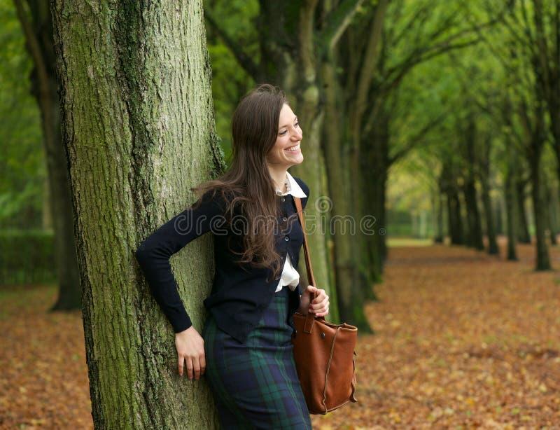 站立户外和放松在一秋天天的愉快的妇女 免版税图库摄影