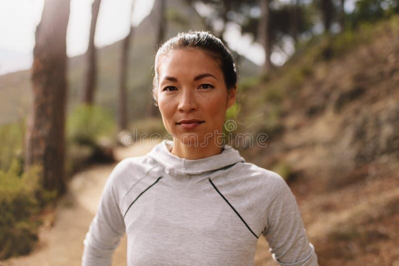 站立户外在乡下公路的妇女赛跑者 库存照片