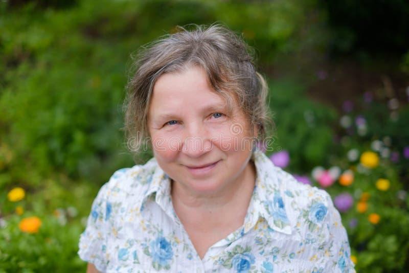 站立户外在庭院里的白种人成熟快乐的成熟妇女画象  她微笑着 免版税库存图片
