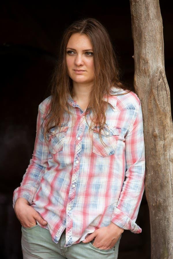 站立户外在木杆的深色的年轻女人 免版税库存照片