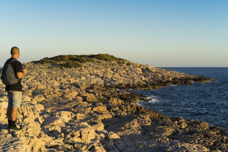 站立户外在石海滩关闭亚得里亚海的人在克罗地亚在日落 免版税库存图片