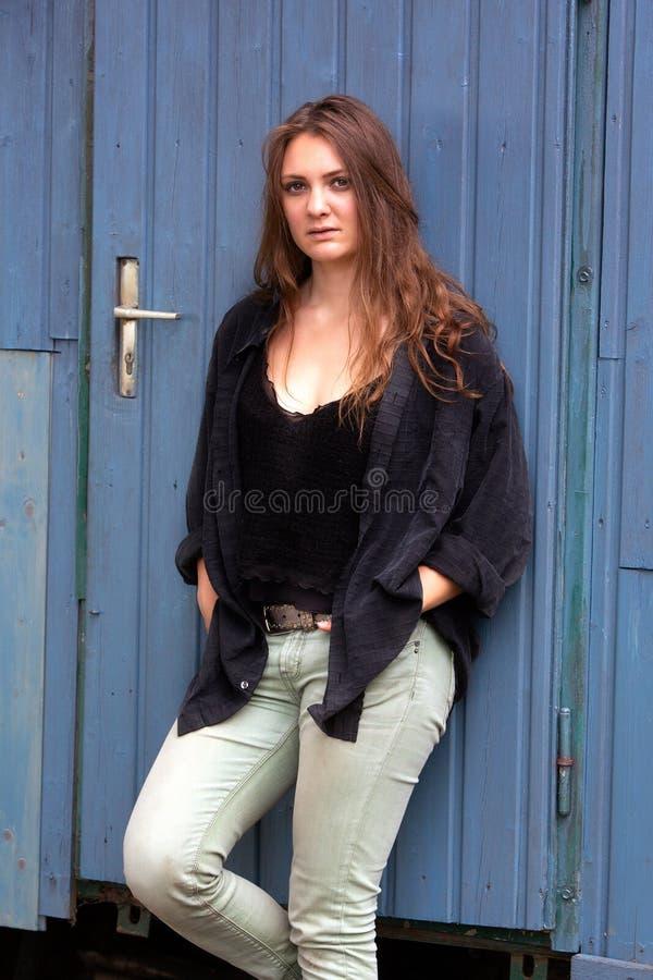 站立户外在蓝色木门的深色的年轻女人 库存照片
