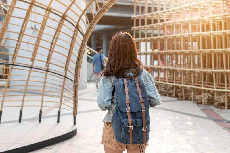 站立户外在都市的后面观点的年轻可爱的亚裔妇女游人 库存照片