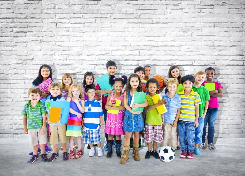 站立接近墙壁的小组小学生 免版税图库摄影