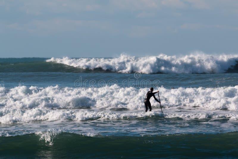 站立明轮轮叶,在船上paddleboarding冲浪者的人 免版税图库摄影