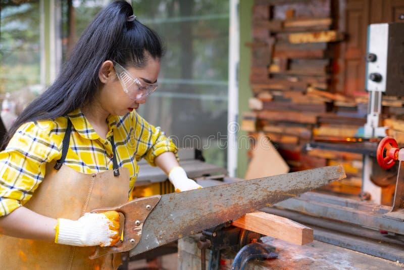 站立是运作被切开的木头的工艺在与圆锯的一个工作台的妇女电动工具在木匠机器 免版税图库摄影