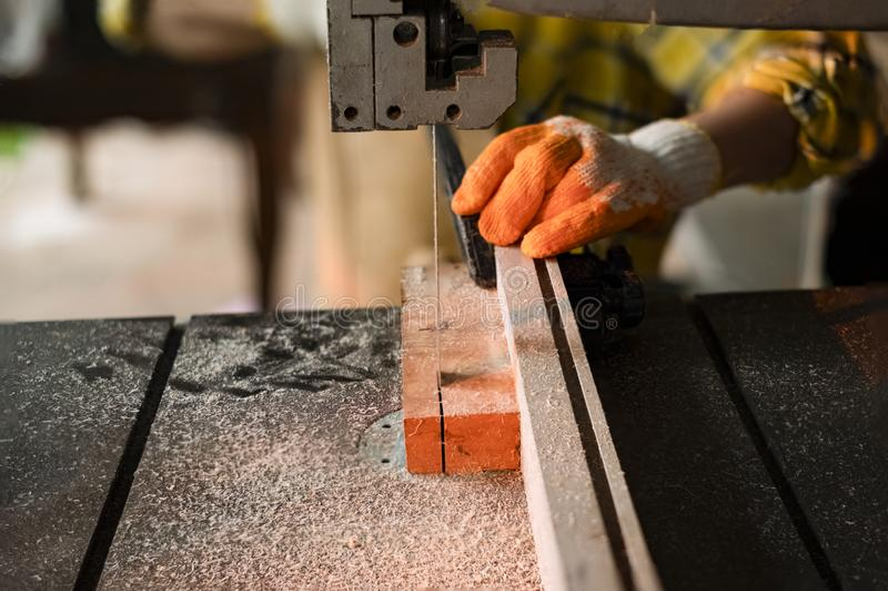 站立是运作被切开的木头的工艺在与带锯的一个工作台的妇女电动工具在木匠机器在车间 免版税库存照片