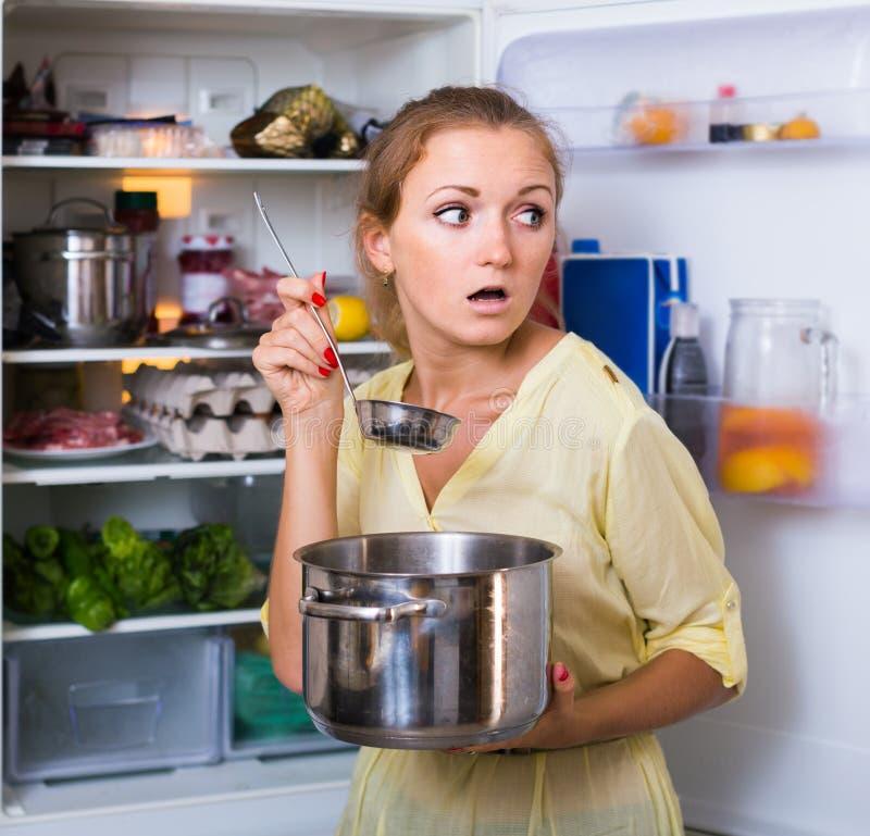 站立有平底锅的饥饿的女性近的冰箱食物 库存照片