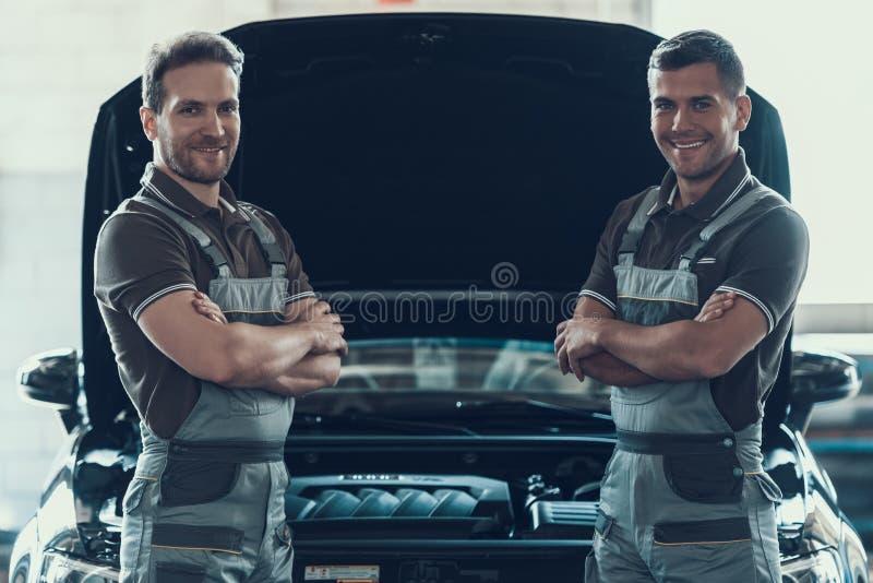 站立有横渡的胳膊的两位技工近的汽车 免版税图库摄影