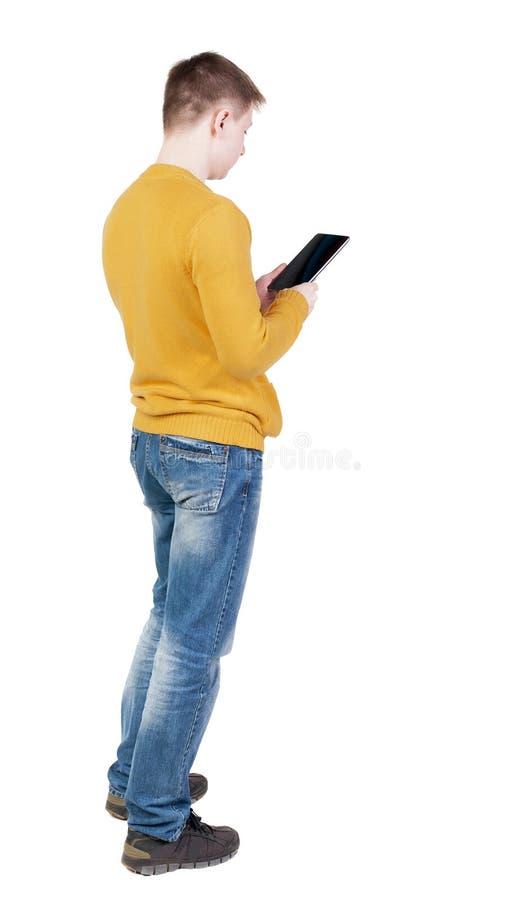 站立有片剂计算机的年轻人后面看法在手上 库存图片
