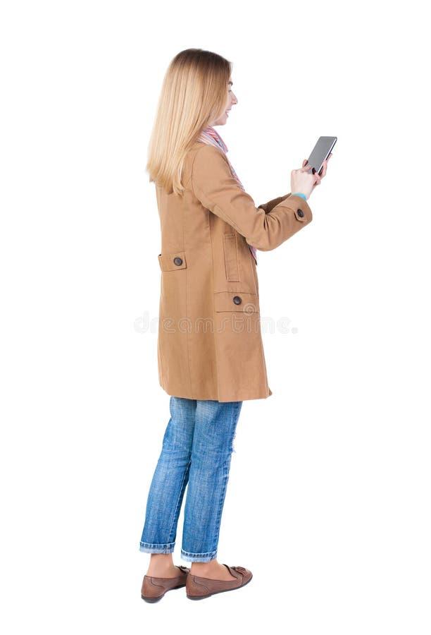 站立有片剂计算机的年轻美丽的女孩后面看法  免版税库存图片