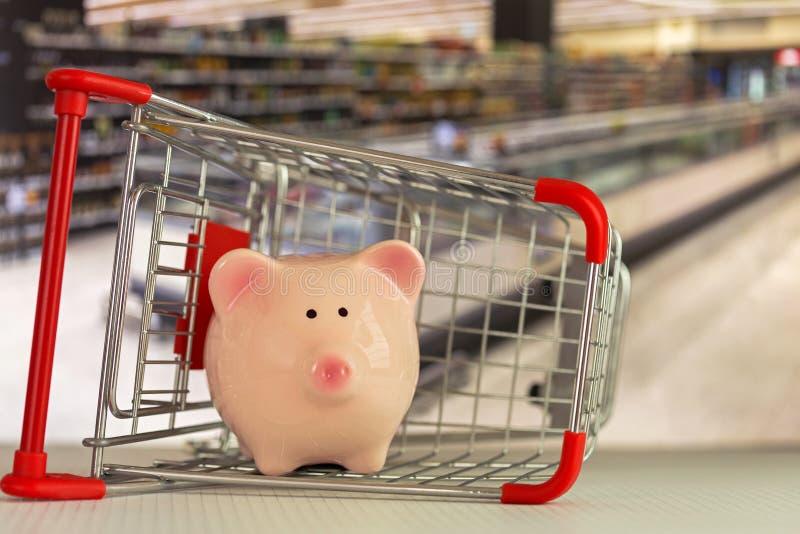 站立有supe的桃红色存钱罐猪里面购物推挤推车 免版税库存图片