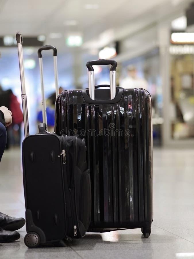 站立机场的黑手提箱 免版税库存图片