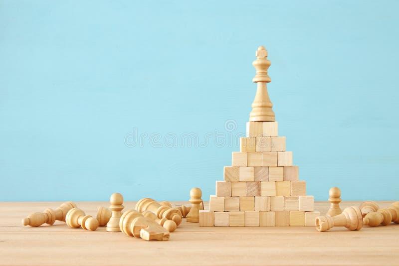 站立棋形象的图象在金字塔上面 事务、竞争、战略、领导和成功概念 库存图片
