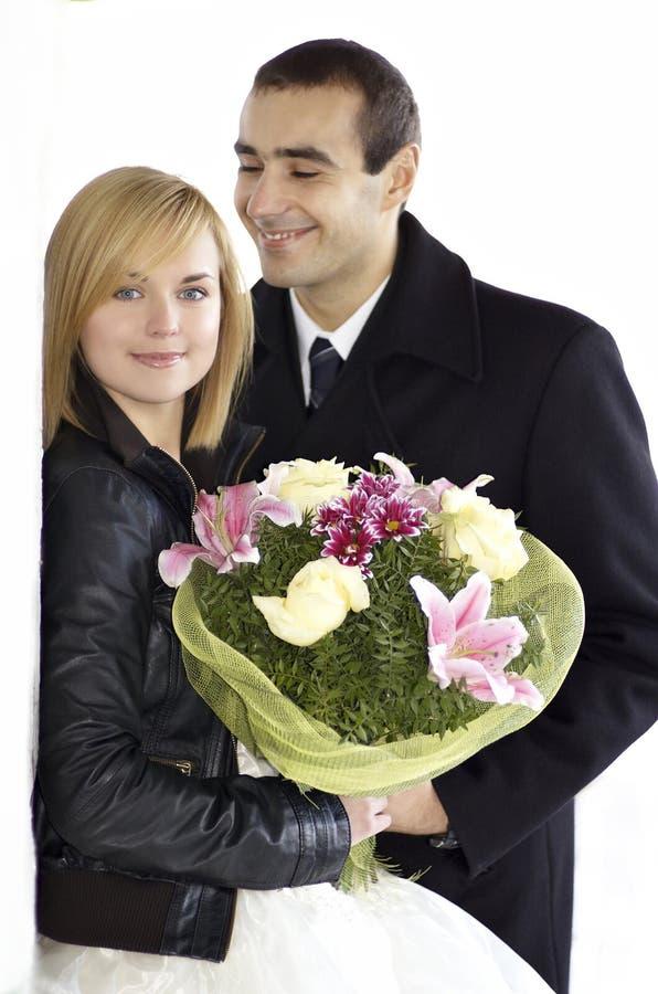 站立浪漫新婚佳偶的夫妇势均力敌在白色backgrou 库存照片