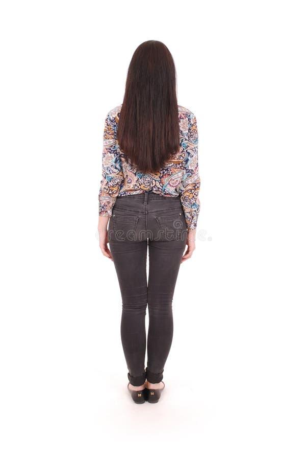 站立牛仔裤的年轻美丽的妇女后面看法  女孩观看 免版税库存图片