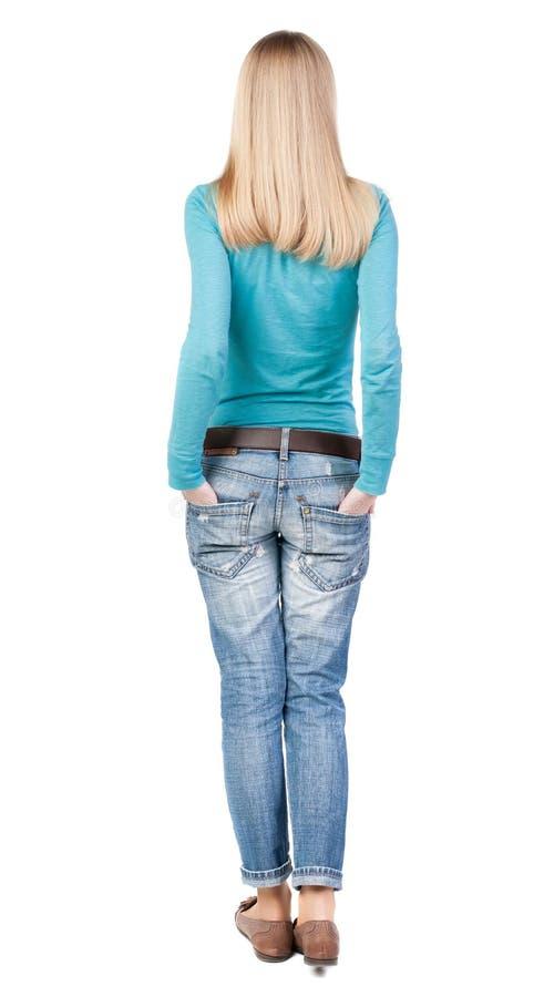 站立牛仔裤的年轻美丽的妇女后面看法  库存图片