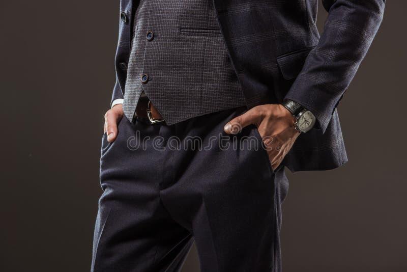 站立用在口袋的手的时髦的商人播种的射击 免版税库存图片