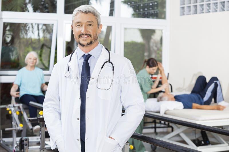 站立用在口袋的手的生理治疗师在健身中心 库存照片