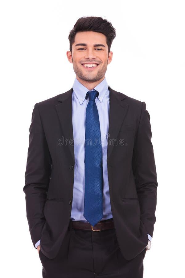 站立用在口袋的手的笑的年轻商人 免版税库存照片