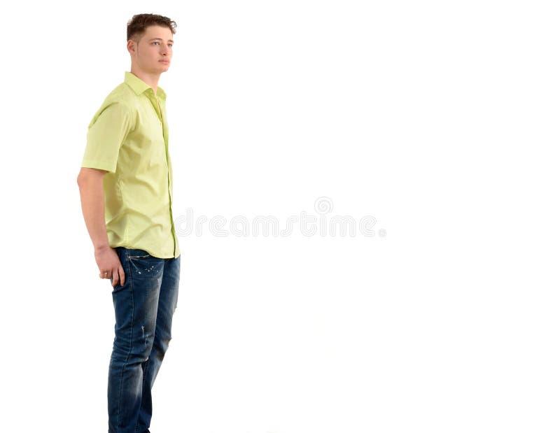 站立用在口袋的手的轻松的人从很远看的外形。 免版税库存图片