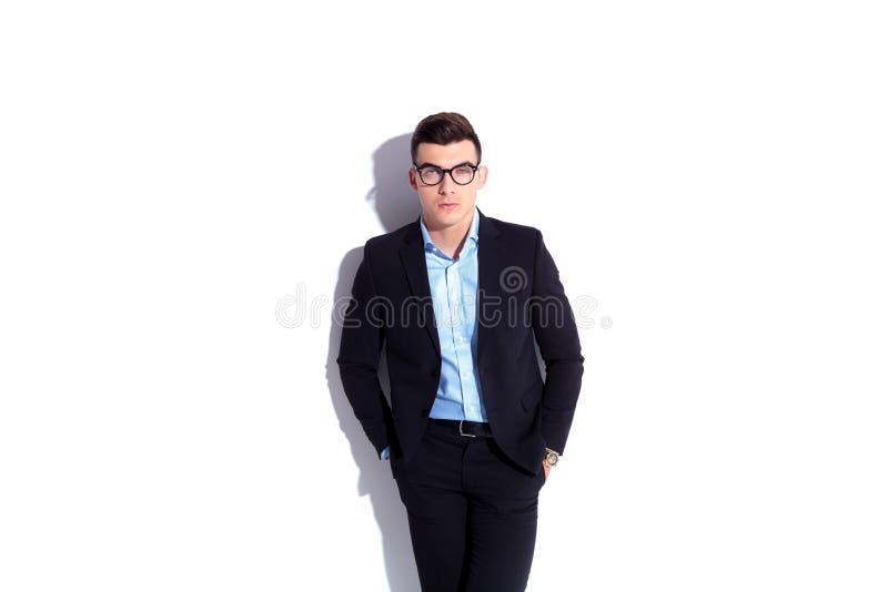 站立用在口袋的手的轻松的年轻商人 图库摄影