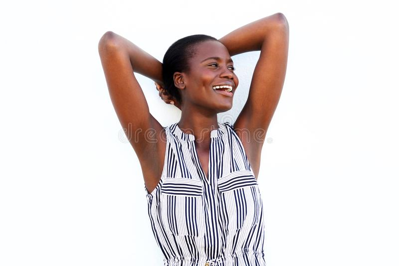 站立用在头后的手的愉快的年轻黑人时髦的女人在白色背景 免版税库存图片