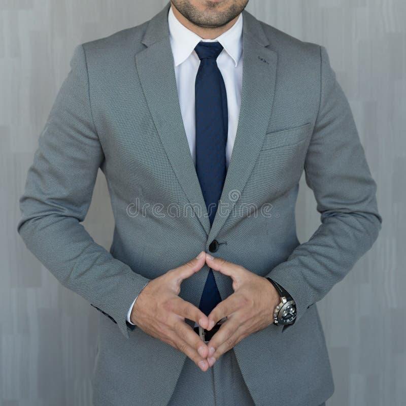 站立用在穿着美丽的时兴的经典灰色衣服的被降下的尖顶的手的匿名商人的躯干 免版税图库摄影