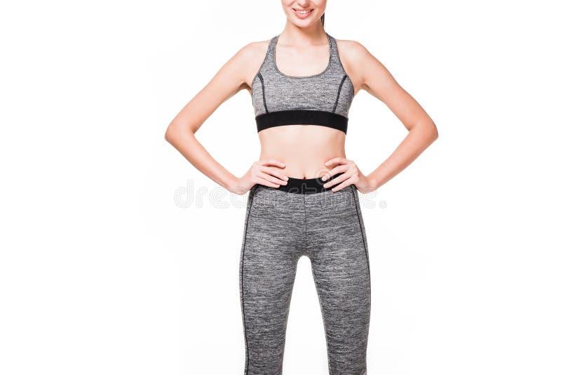 站立用在腰部的手的微笑的女运动员播种的射击 免版税图库摄影