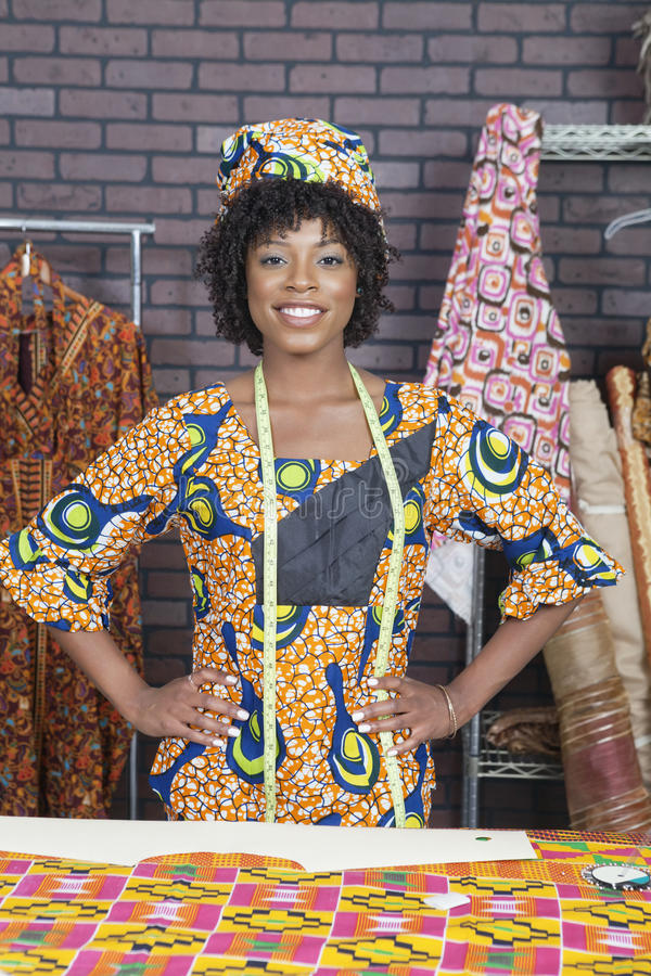 站立用在臀部的手的俏丽的非裔美国人的女性时装设计师画象  免版税库存图片
