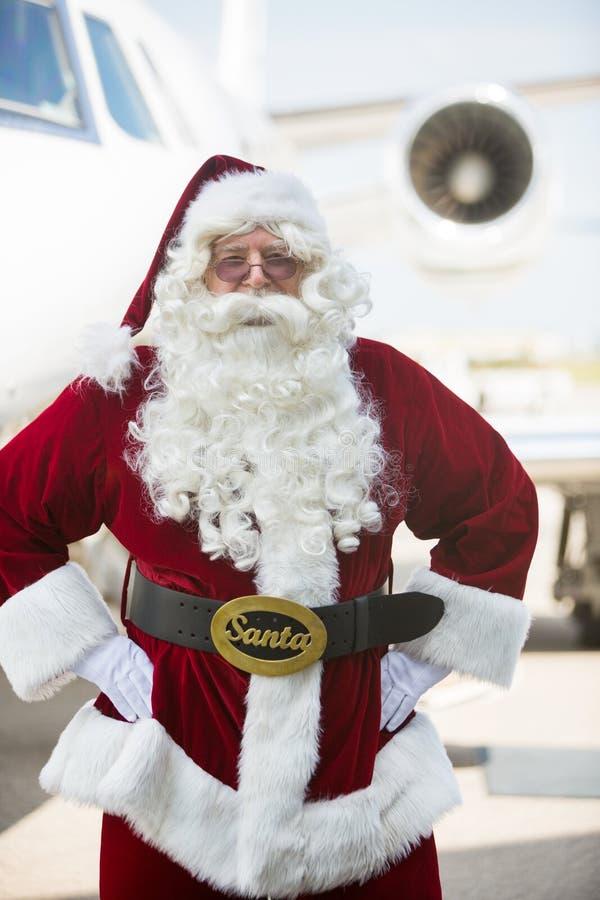 站立用在臀部的手的圣诞老人反对私有 库存照片