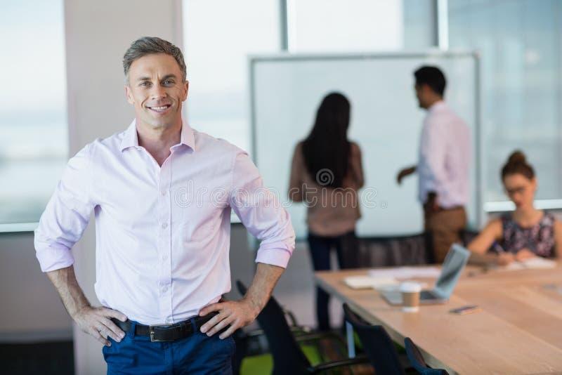 站立用在臀部的手的微笑的商业主管画象在会议室 免版税图库摄影