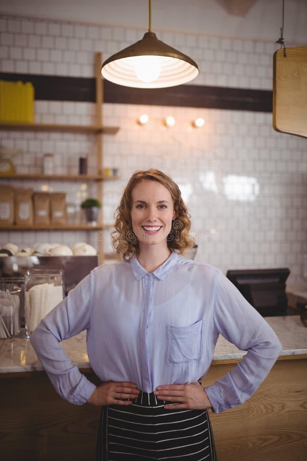 站立用在臀部的手的微笑的年轻女服务员画象反对柜台 免版税库存照片