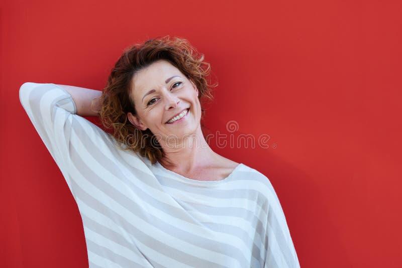 站立用在头后的手的妇女在红色墙壁旁边 免版税库存图片
