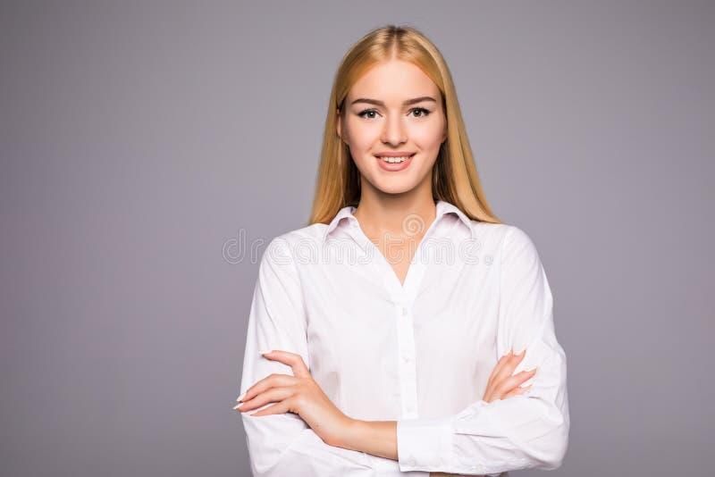 站立用手被折叠和看在白色背景的美丽的女商人画象照相机 免版税库存照片