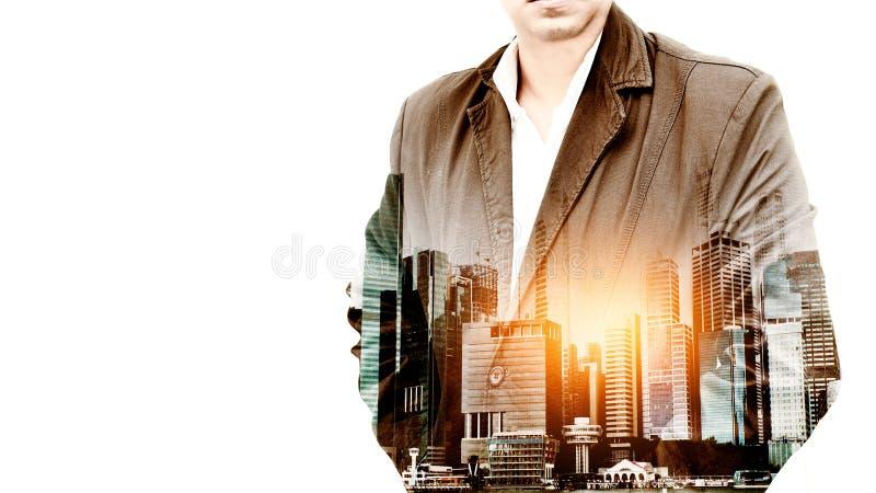 站立用他的在口袋的手的一个确信的有胡子的商人的画象躺在了城市风景背景 双重exposur 图库摄影