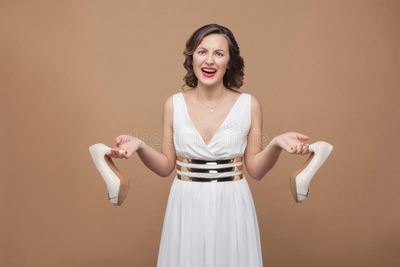 站立白色的礼服的恼怒的女商人看照相机s 免版税库存图片