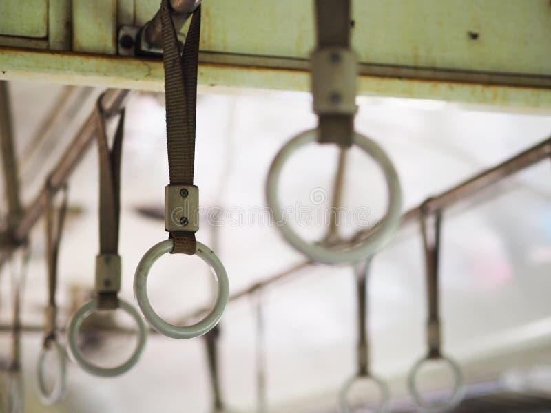 站立的乘客的圆的把柄在老经济舱火车里面 免版税库存照片