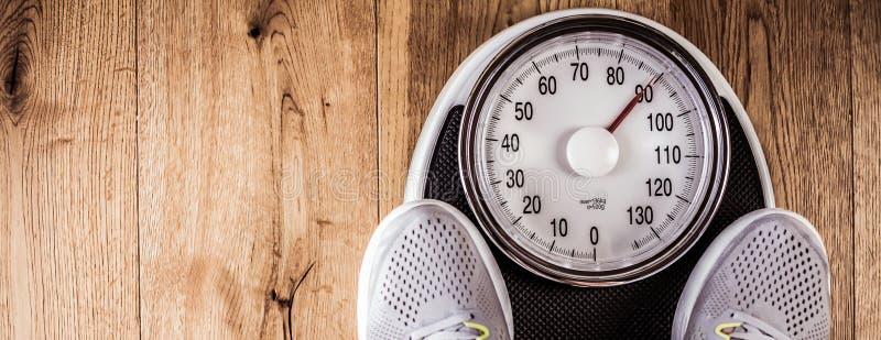 站立的人称标度在健身房 由卷尺的腰围尺寸 概念健康生活方式 免版税库存照片