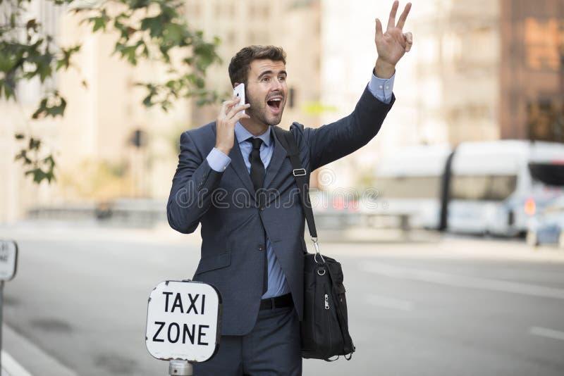 站立的商人称赞出租车 免版税库存照片