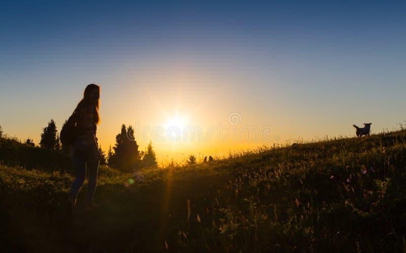 站立的日落或的日出的愉快的庆祝的赢取的成功妇女兴高采烈与胳膊在她的头上上升了  免版税库存图片
