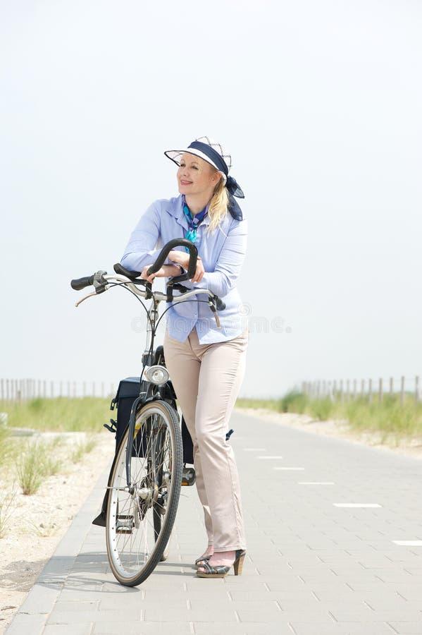 站立的老妇人松弛与在道路的自行车 库存图片