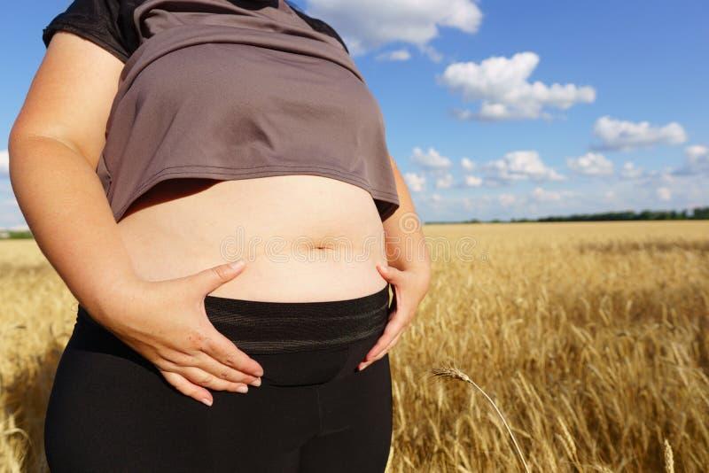 站立的运动服的肥胖妇女户外 库存照片